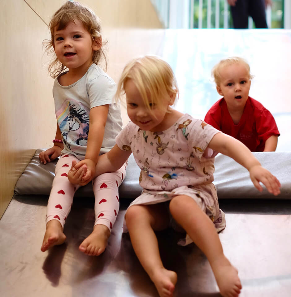The Brook Early Education and Care - Toddlers Sliding down an indoor slide