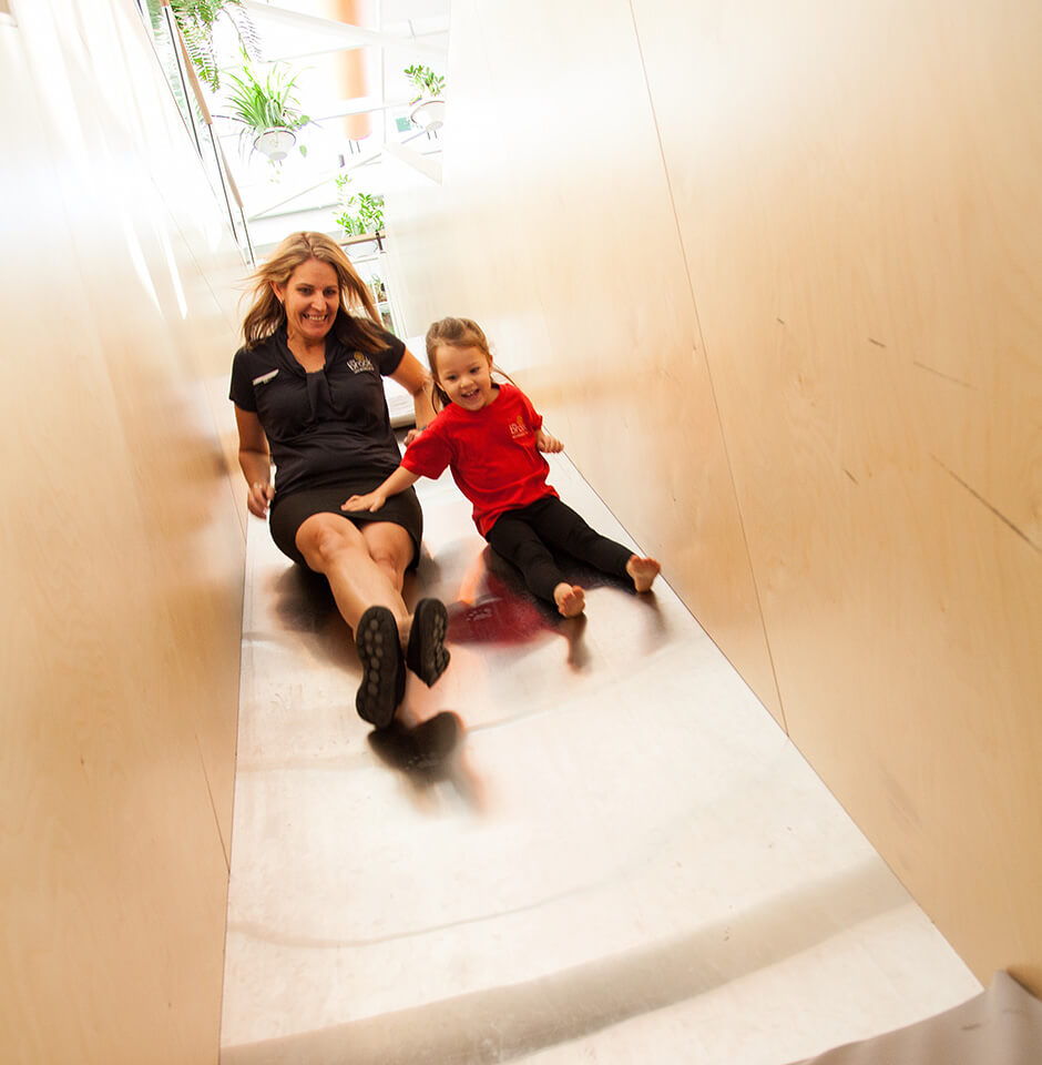 The Brook Early Education and Care - Educator and Toddler Sliding down an indoor slide