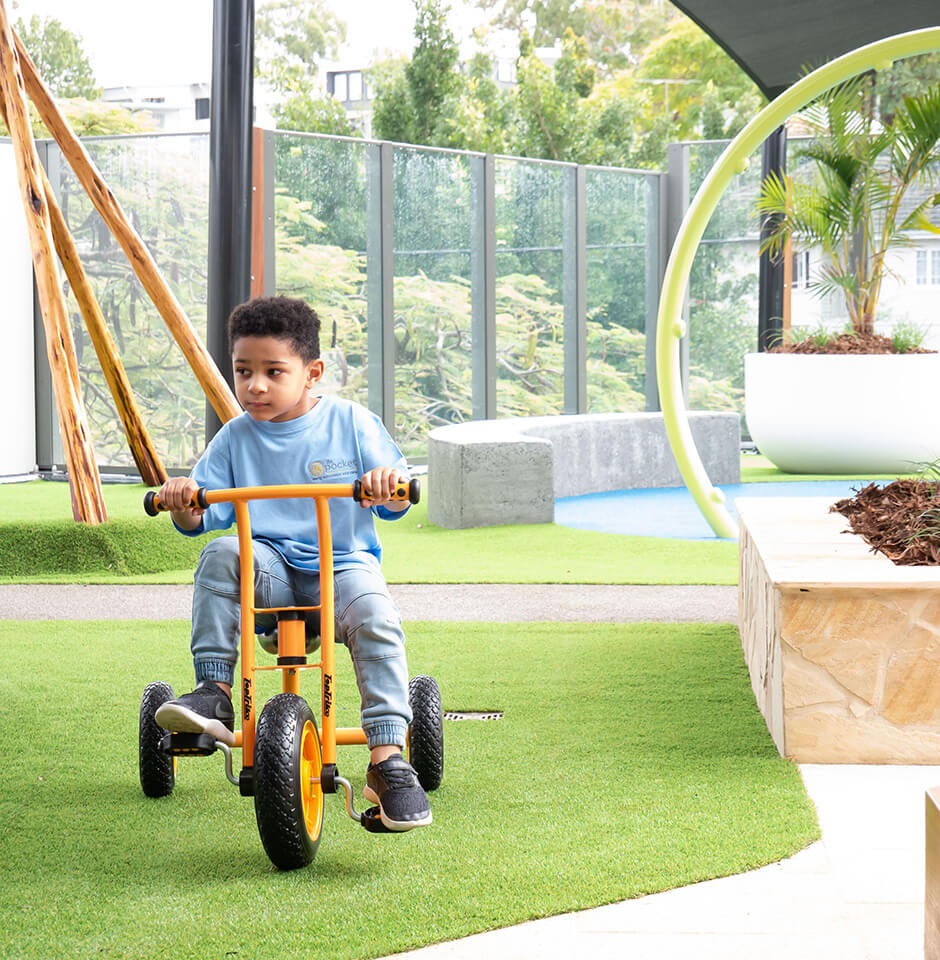 The Pocket Early Education and Care - Boy riding tricycle outdoors